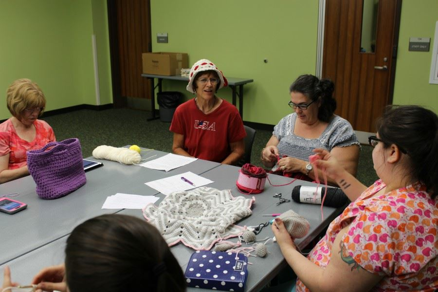 Women talking at crocheting at table at Library